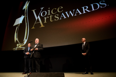 J. Michael Collins accepting voice arts award on stage
